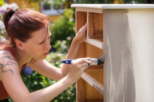 Frau streicht Möbel aus Holz mit Kreidefarbe, Shabby chic und Vintage