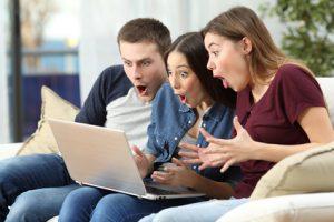 Cyber Week: drei Freunde erstaunt vor dem Computer